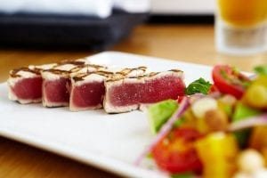 plate of sliced tuna seared on the outside and raw on the inside