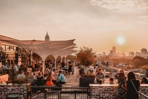 people enjoying food and beverages, as the sun sets, on the 9 Mile Station rooftop patio