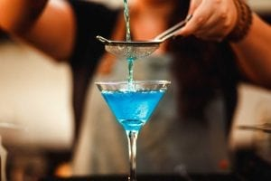 bartender pouring blue cocktail into martini glass