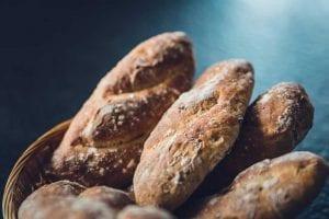 bread loafs in a basket on a blue background