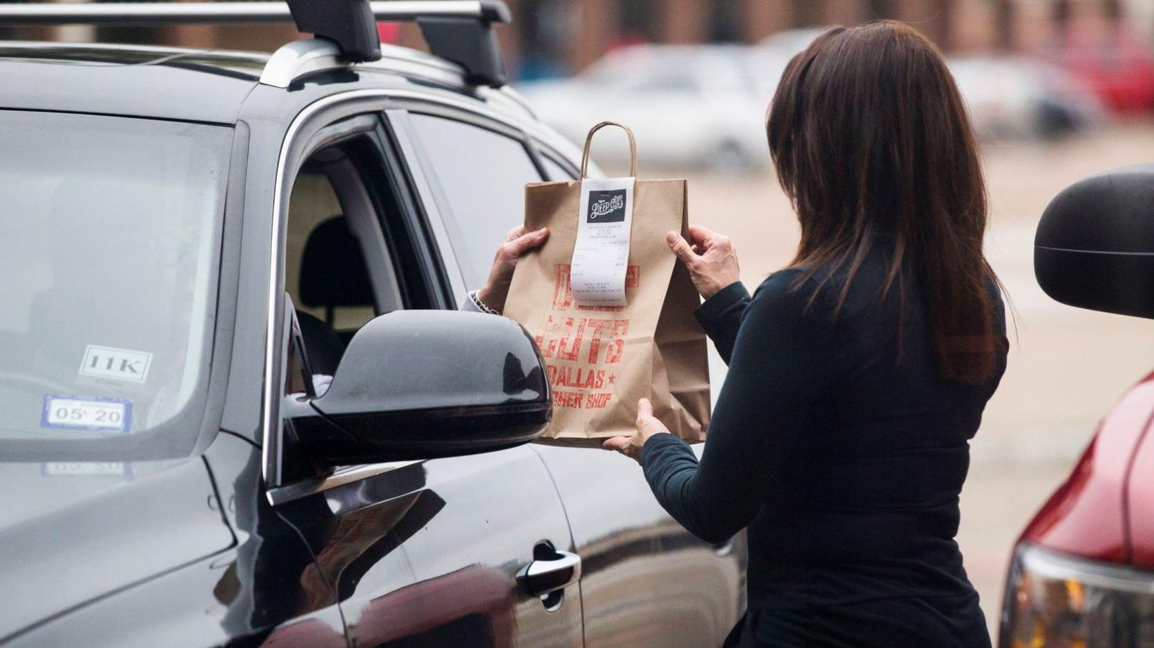 delivering bag of food to curbside pickup