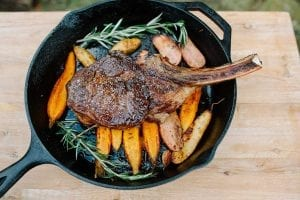 photo of steak over sweet potatoes in a cast iron skillet