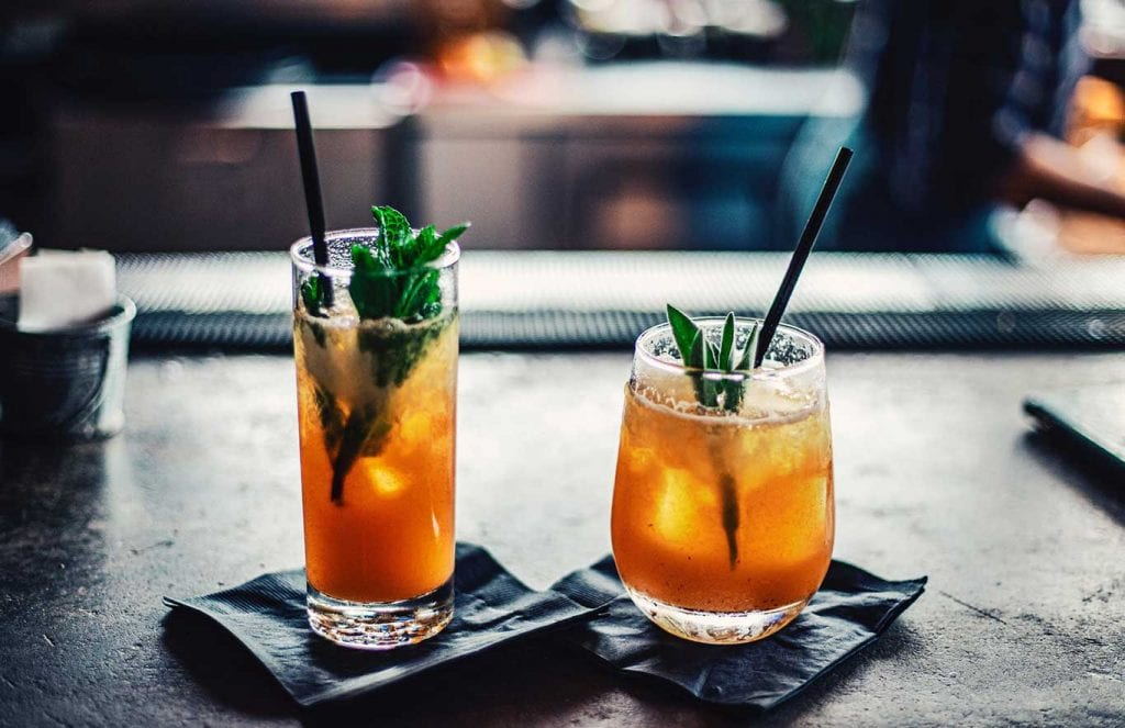 Two cocktails sitting on a bar
