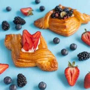 Two layered croissants surrounded by fruit