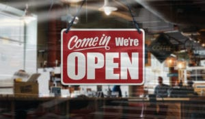 come in we're open sign handing in coffee house window