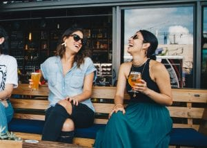 two women enjoying beers and laughing on a bench