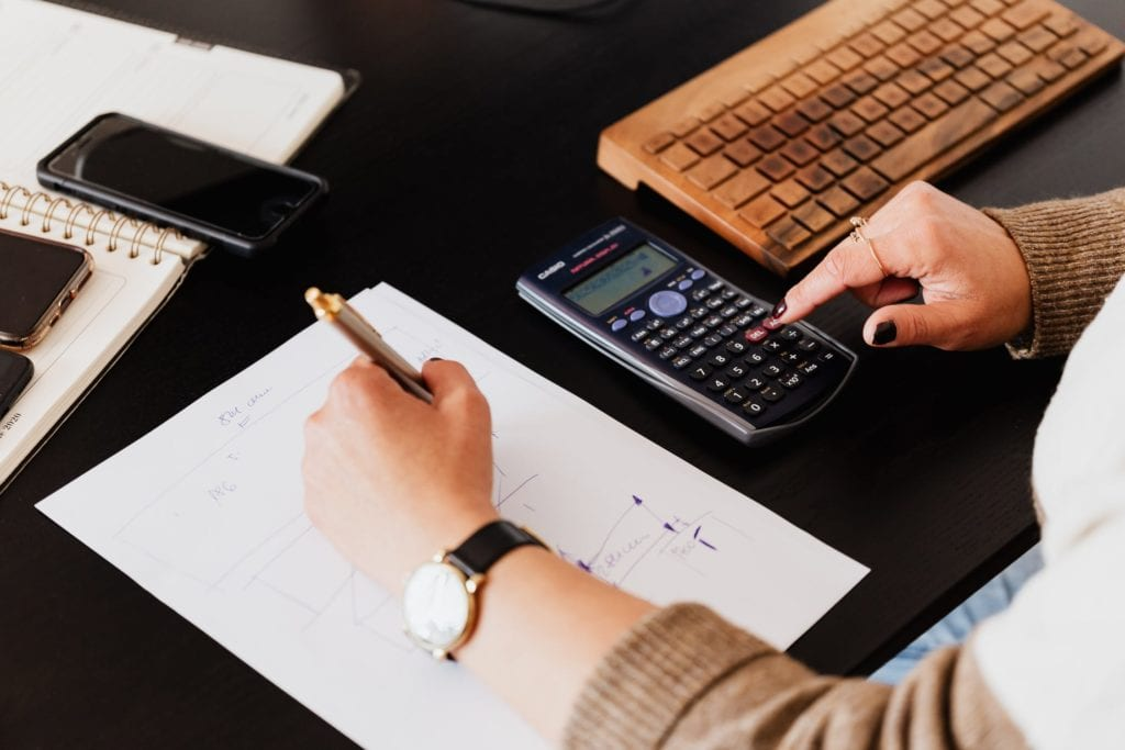 woman writing and working with calculator