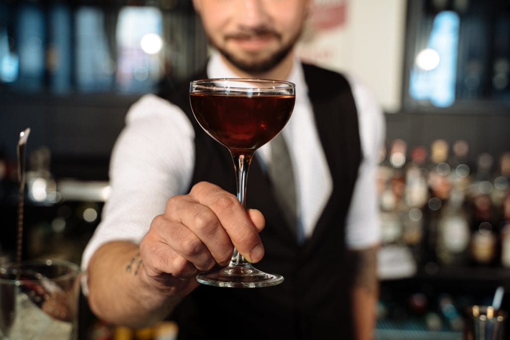 bartender serving camera a cocktail