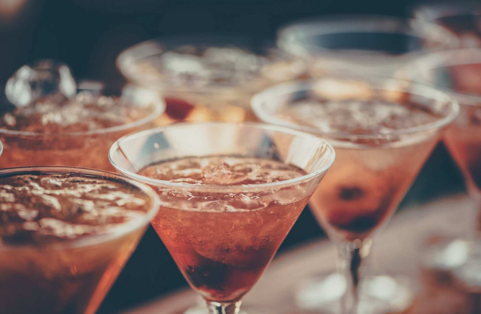 red cocktails with ice in martini glasses